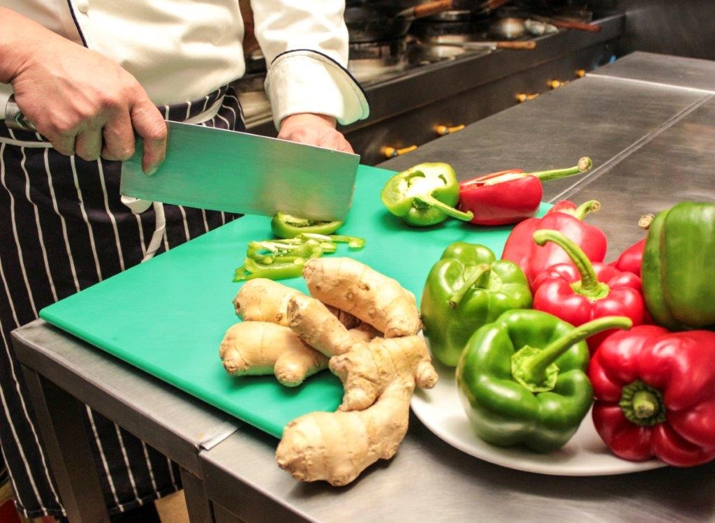 Chef cutting green peppers