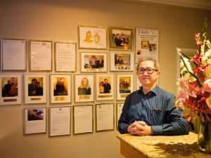 Image of founder with testimonials & photos on wall