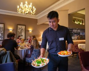 Headwaiter serving dishes